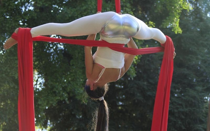Girl doing aerial tricks with red ribbon.