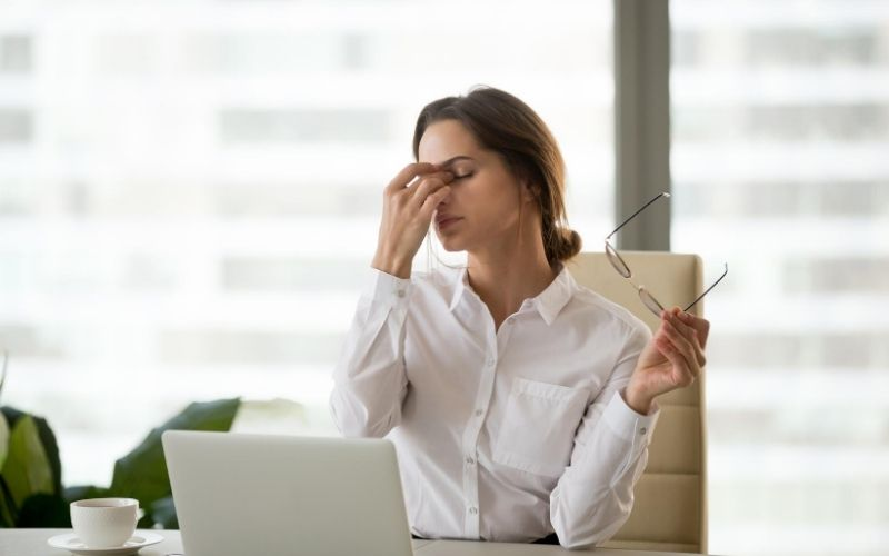Woman scratching her dry eyes.