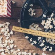 Film wheel with a bag of popcorn on a wood table.
