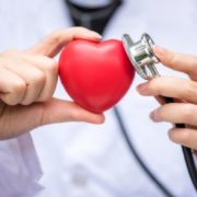 Doctor holding toy heart with stethoscope.