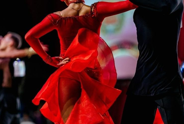 Woman in red dress and her male partner dancing in competition.