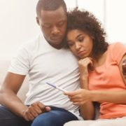 Couple looking down at pregnancy test.