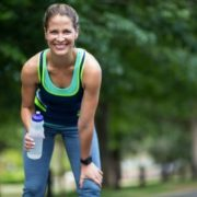 Woman holding water bottle smiling in running clothes.
