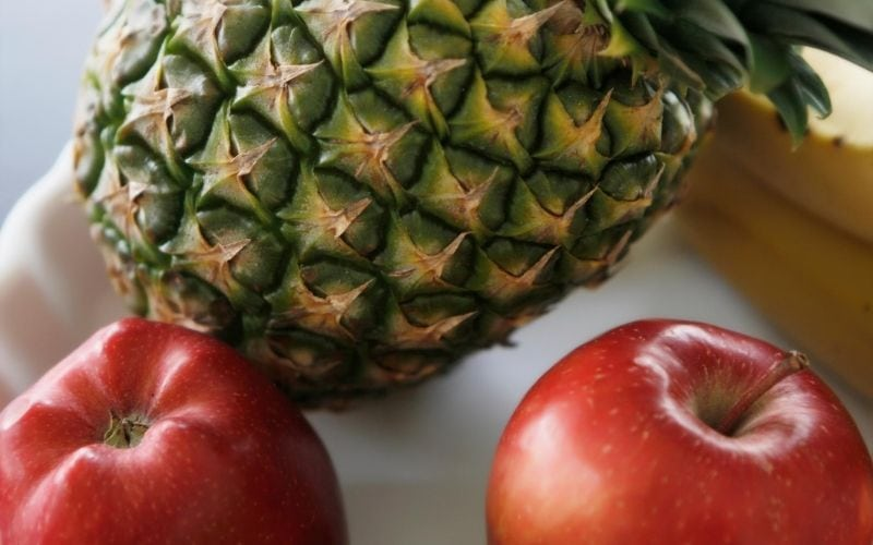 two apples and a pineapple on a table.
