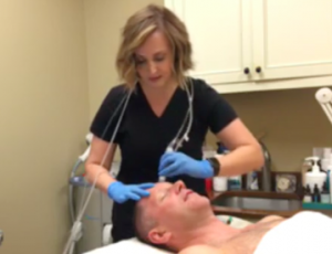Tonya Grismer L.M.E. exfoliates David's skin to prep it for the Hyaluronic Acid.