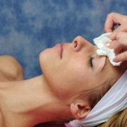Woman getting face peel removed with cotton pad.
