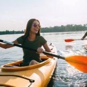 Girl kayaking with friend on lake.