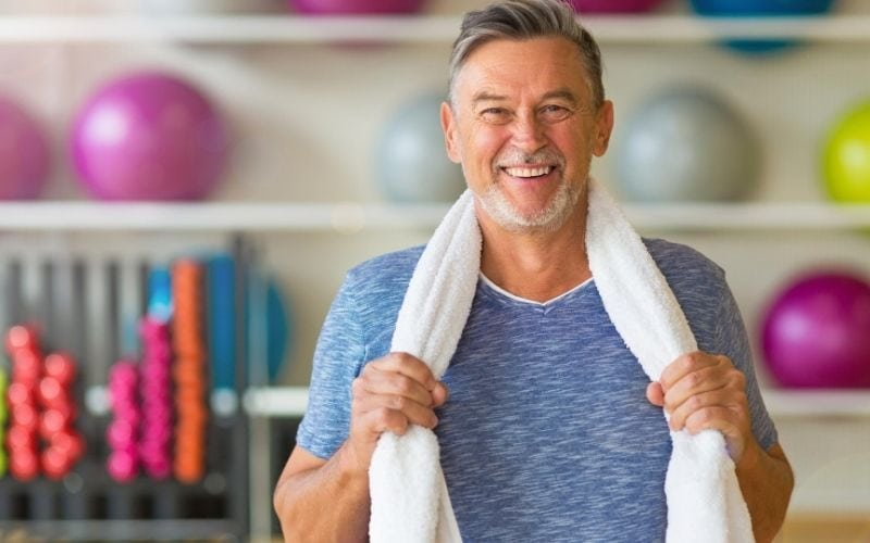 Man in gym with towel around his neck.
