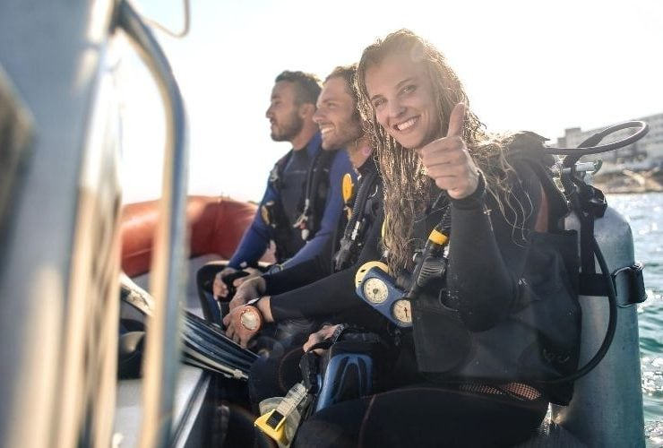 Woman and friends on a boat in scuba diving gear.