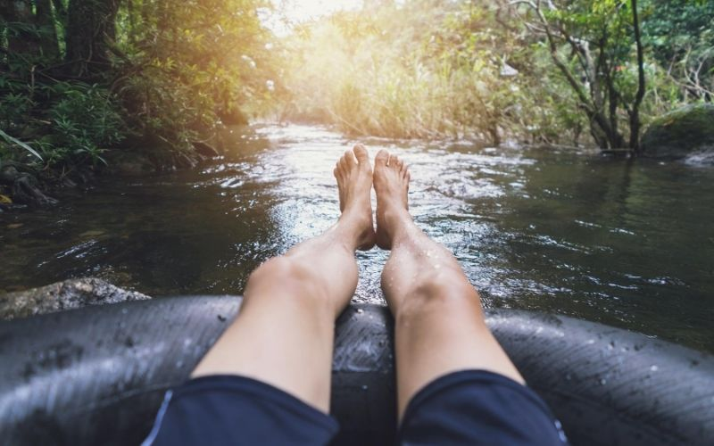 Man in tube floating down a river.