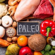 "Fruits, vegetables and grains surrounding chalkboard that says ""Paleo""."