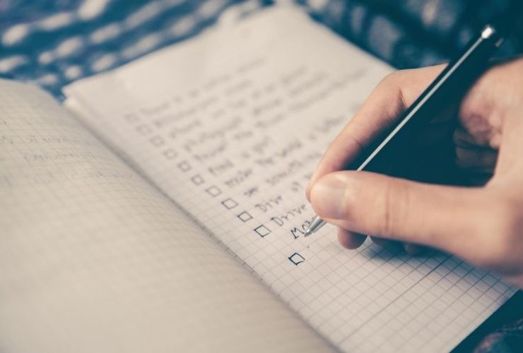 Person writing down their goals on a notepad.