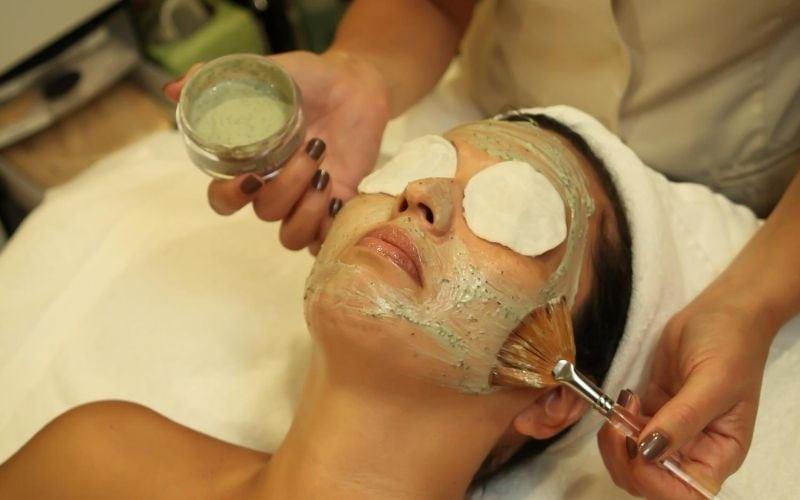 Woman getting facial mask at spa.