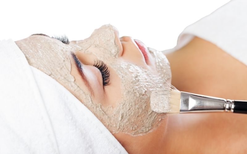 Woman getting a mask during facial.