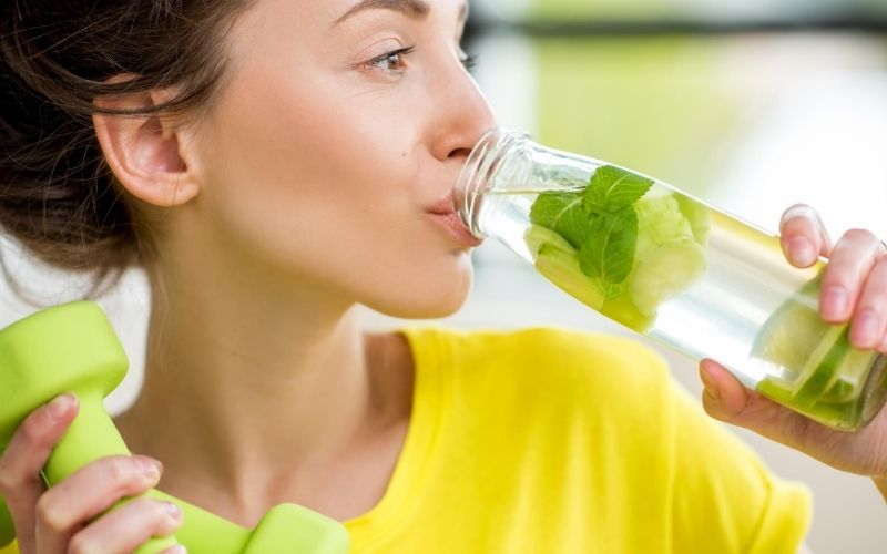Healthy woman drinking water.