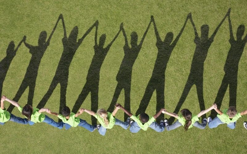 Children holding hands in grass with shadows.