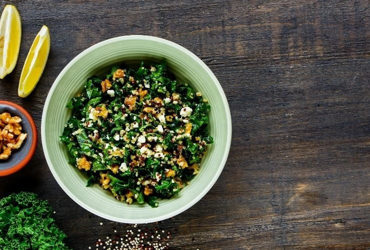 Kale and quinoa bowl with sliced lemon and nuts on the side.