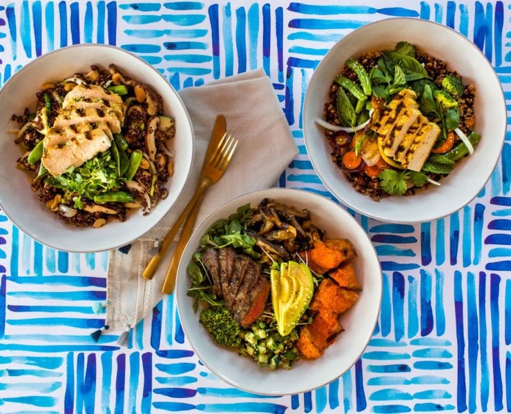Different bowls of healthy food on blue striped table cloth.