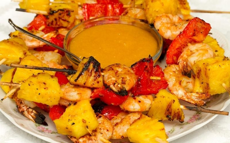 Pineapple and shrimp skewers with sauce.