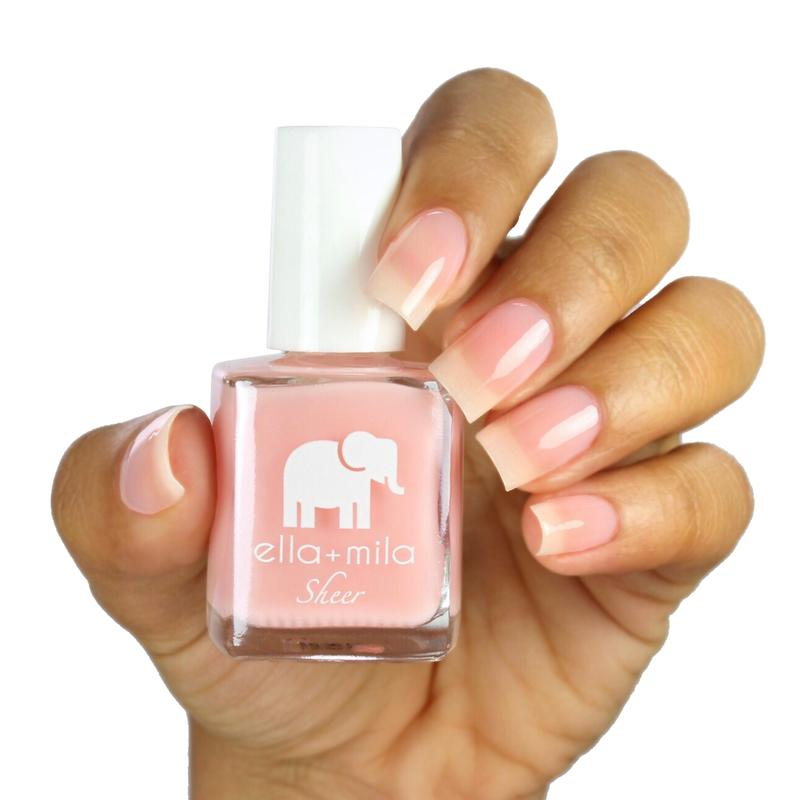 Pink nail polish being held in hand.