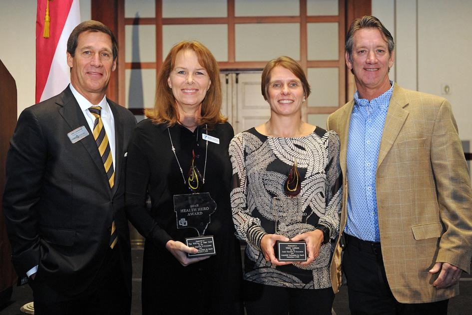 Four people standing together holding awards.