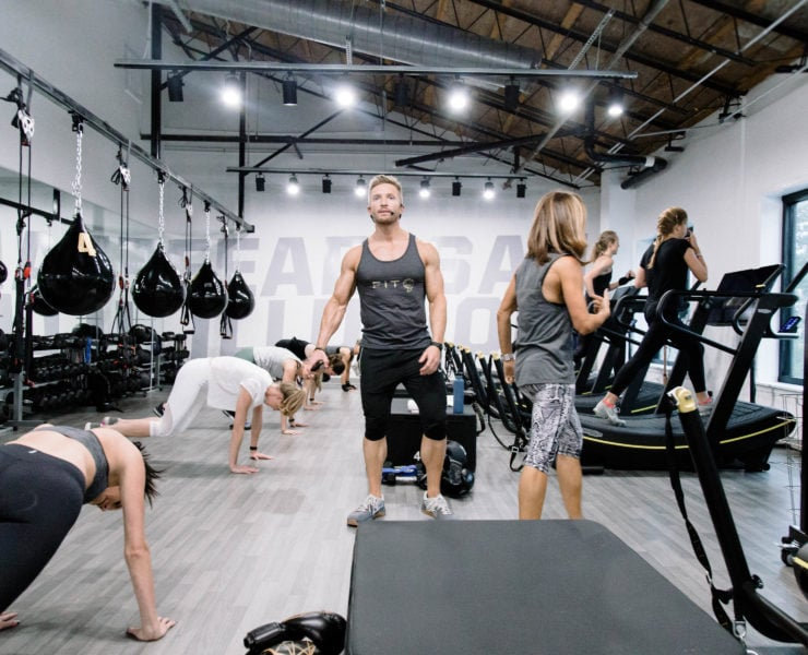 Workout instructor leading a circuit class in gym.
