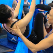 Aerial instructor holding student up while doing workout.
