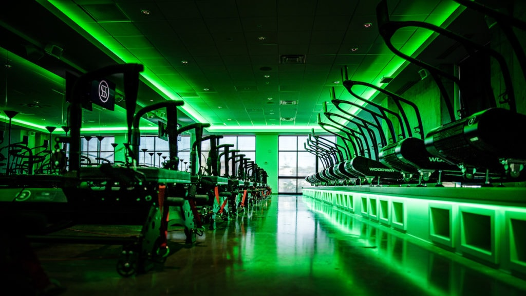 Green neon lights in SculptHouse's workout room.