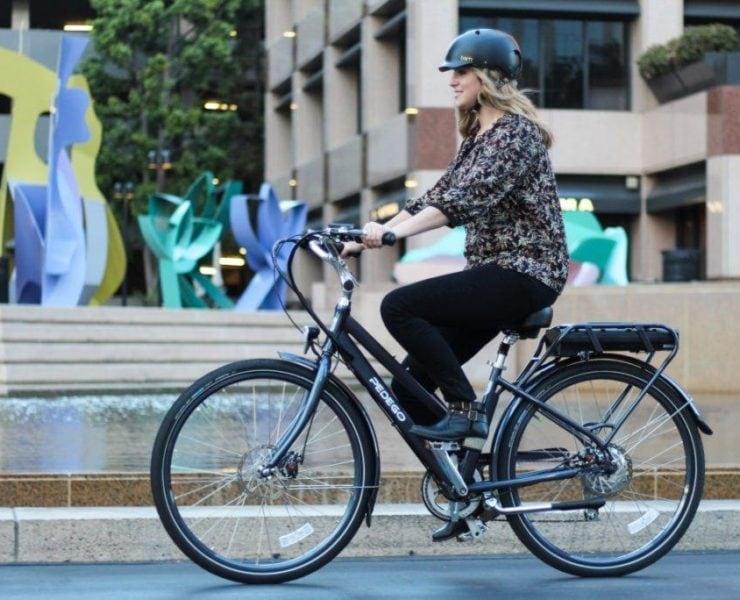 Woman riding electric bike through city.
