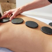 Woman on massage table getting a hot stone massage.