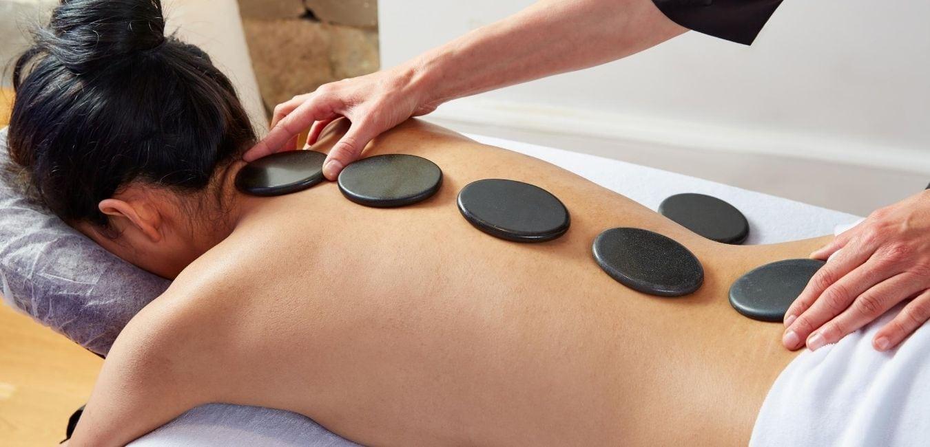 Woman on massage table getting a hot stone massage.