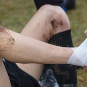 Athlete getting ankle wrapped on the field.