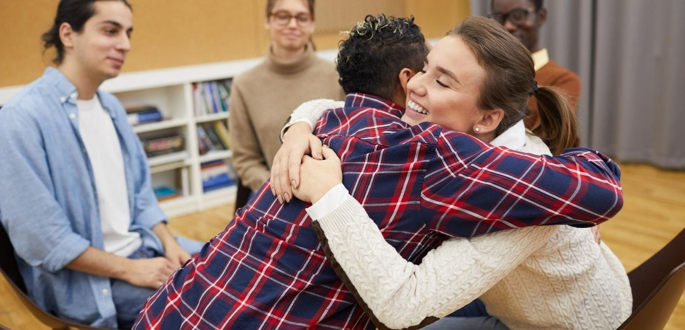 Teenagers hugging in group setting.