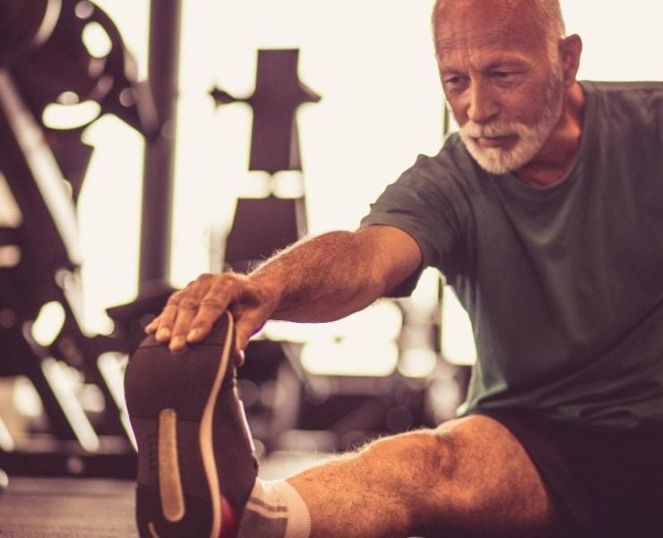 Man stretching in a gym.