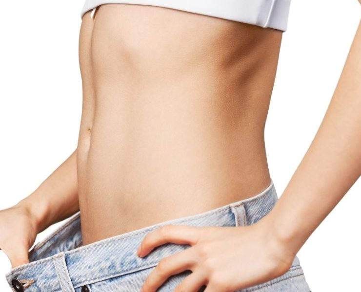Woman pulling front of jeans showing her trim belly