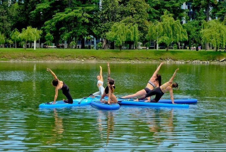 Women doing yoga on paddle boards.