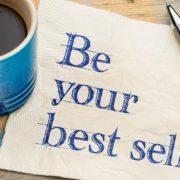"""Be your best self"" on napkin beside a pen and coffee mug."