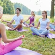 Yoga instructor leading a group outside.