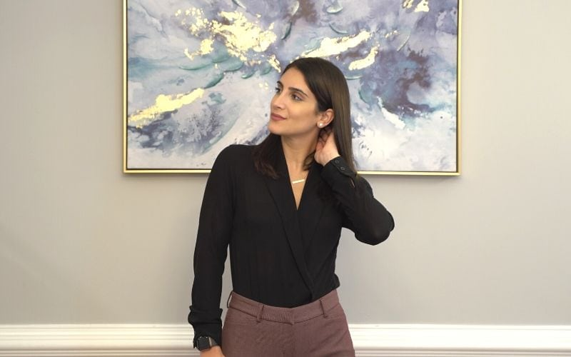 Woman styling a black body suit in front of a painting