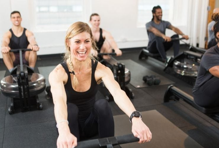 Woman in the front row of a class working on row machines