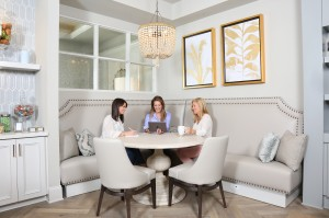 Women sit and chat around a table