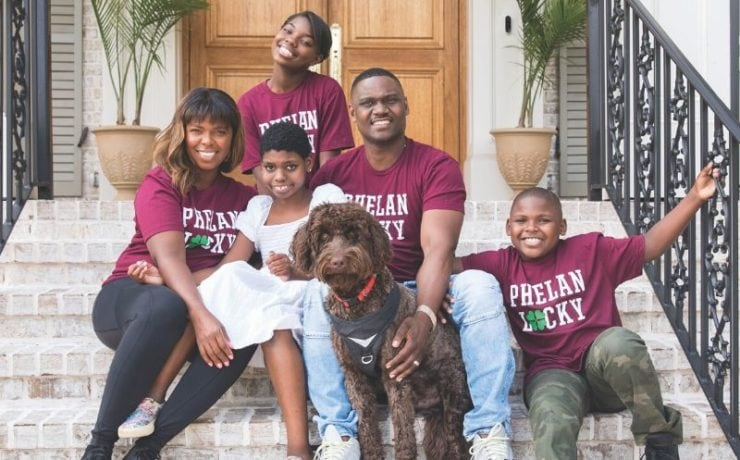 A family of five with a brown dog on a front porch steps