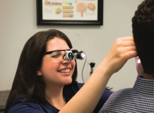 DR. MELISSA WIKOFF (LEFT) LOOKS INSIDE A PATIENT'S EAR.