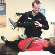 Physical Therapist from Benchmark PT assisting a patient with stretches
