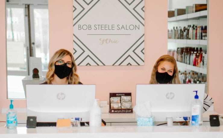 Two women stand in front of receptionist desk at Bob Steele Salon with masks