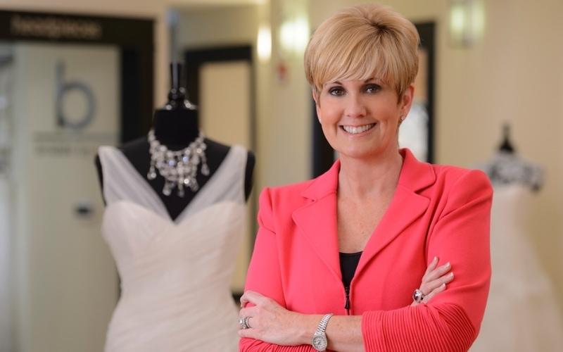 Lori Allen in front of dresses