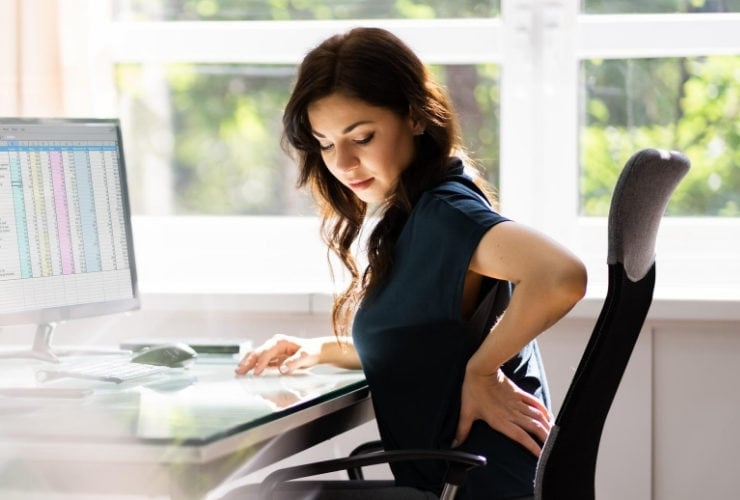 Woman experiencing back pain at the computer