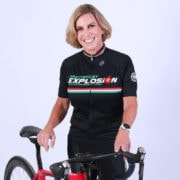 Woman in bike gear posing in photo with her bike.