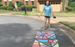 A girl showing off her colorful, geometrical sidewalk chalk art.