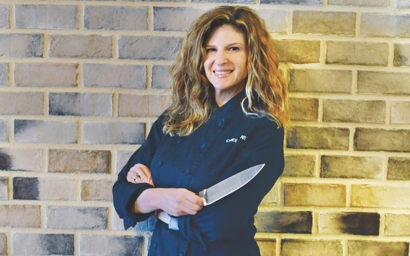 Woman standing with her arms crossed smiling in black chef coat.